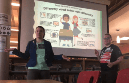 Two people stand before a presentation, speaking to the audience