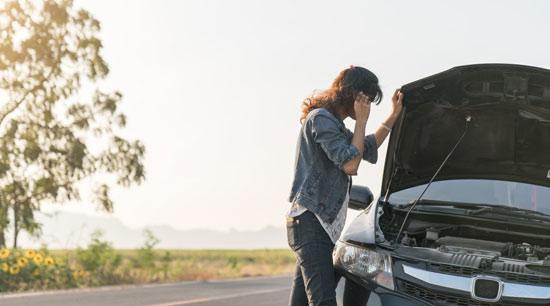 Woman stranded on roadside with dead car battery