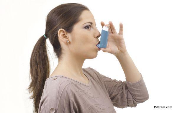portrait of young women woman using asthma inhaler