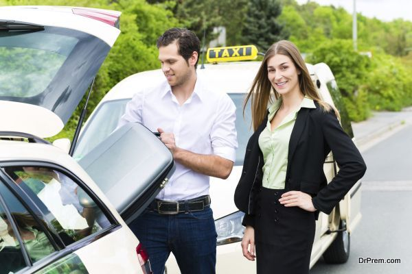 Young businesswoman in front of taxi with luggage