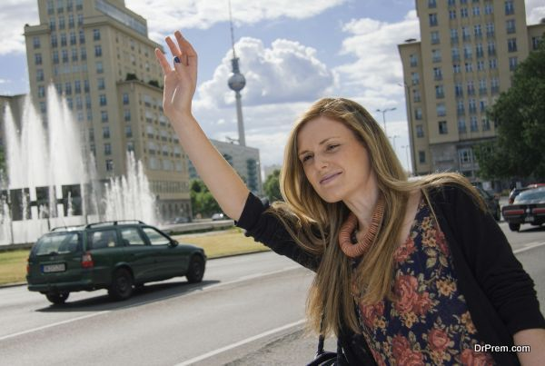Young professional female in Berlin hailing at cab
