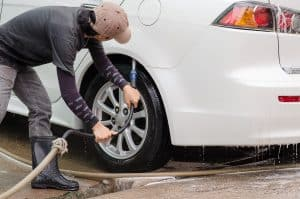 Car washing.A man cleaning wheels using high pressure water jet at car wash station.