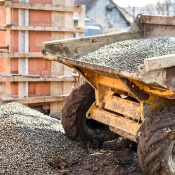 Dumper truck unloading construction gravel, sand and crushed stones