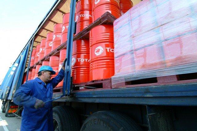 Vue extйrieure de l'usine de lubrifiants de Rouen. Un employй vйrifie que les fыts et les bidons rouges de lubrifiants Total qui viennent d'кtre chargйs sur le camion sont bien attachйs et prкts а кtre livrйs.