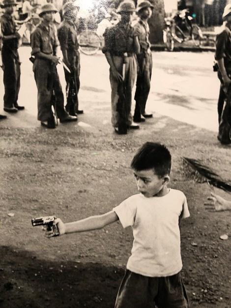 photographie de Marc Riboud : enfant s'amusant avec un pistolet-jouet dans les rues de Hanoi Nord-Vietnam 1969