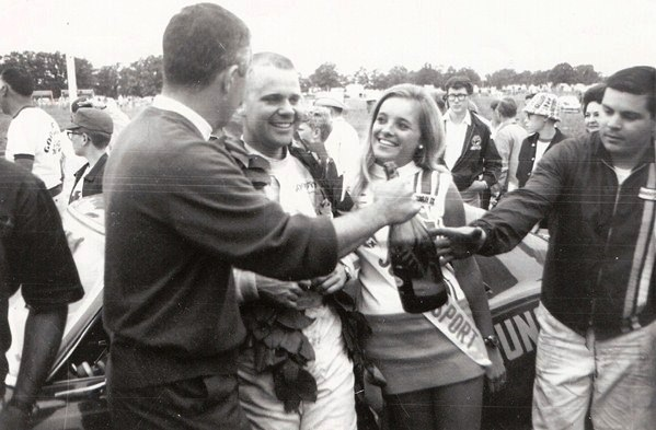 LtoR-Roger-Penske-Mark-Donohue-trophy-girl-Ron-Fournier