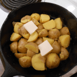 baby yukon potatoes in cast iron skillet with butter
