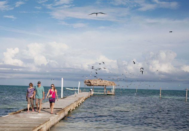 A family of tourists walks down one of the many rough wooden docks along the shores of Caye Caulker. Photo: Alex Washburn