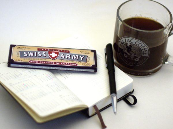 """Caffeine - Auf einem Notizbuch liegt eine Tafel """"Swiss Army"""" Schokolade mit Koffein und ein Kugelschreiber. Daneben steht eine durchsichtige Tasse die Kaffee enthält."""