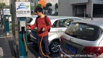 Китаец у зарядной станции для автомобилей