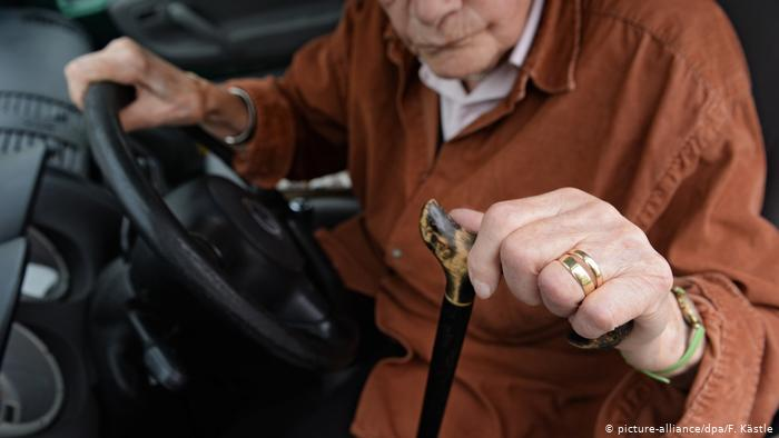 Пожилой человек с палочкой садится в автомобиль