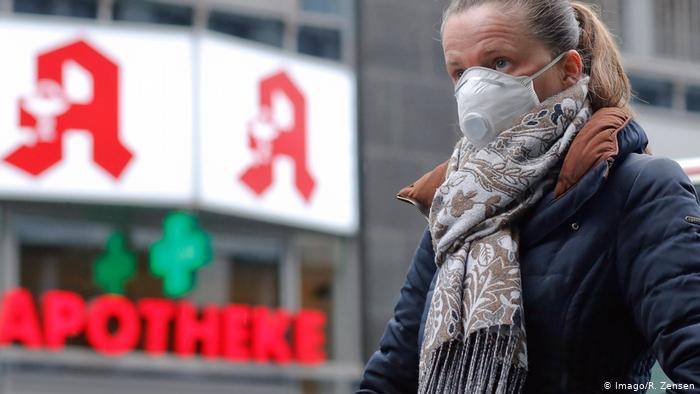 Женщина в Берлине идет по улице с защитной маской на лице, которая, как она надеется, поможет ей избежать заражения коронавирусом.
