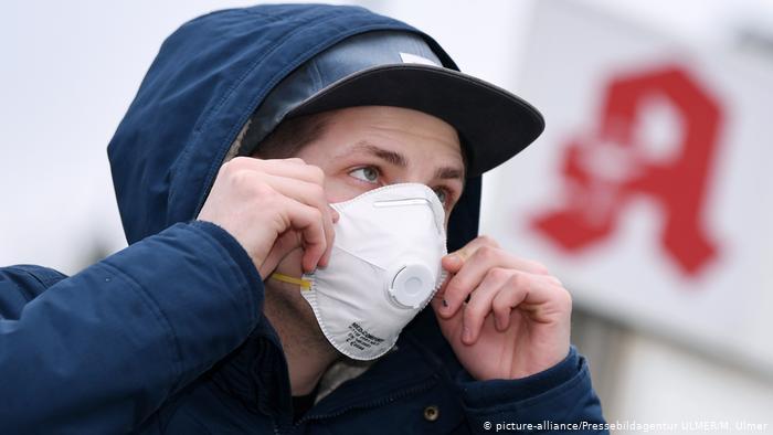 Молодой человек в защитной маске на фоне вывески аптеки