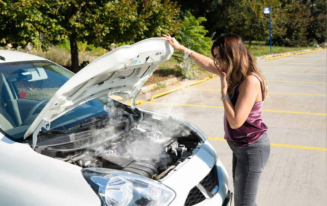 a woman's car breaks down with smoke coming from the engine