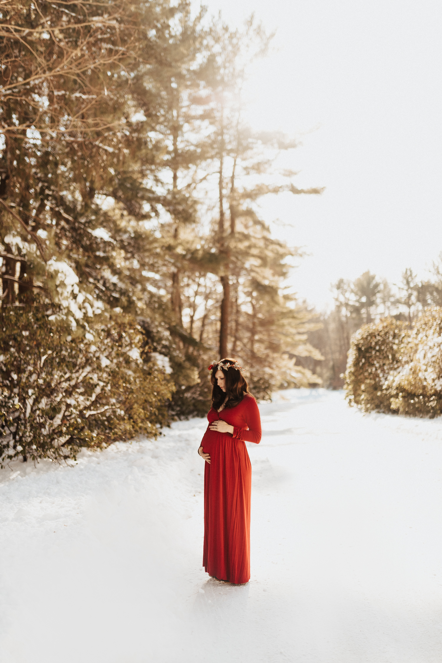 Expecting Mama in a red dress and flower crown during sunset and in the fresh snow