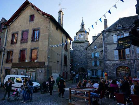 Besse-et-Saint-Anastasies-brasseries-and-old-town-shops-overlooked-by-the-historic-town-belfry.-Image-by-Anita-Isalska
