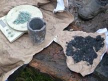 Stacking the crucible with layers of charcoal dust and copper ore.