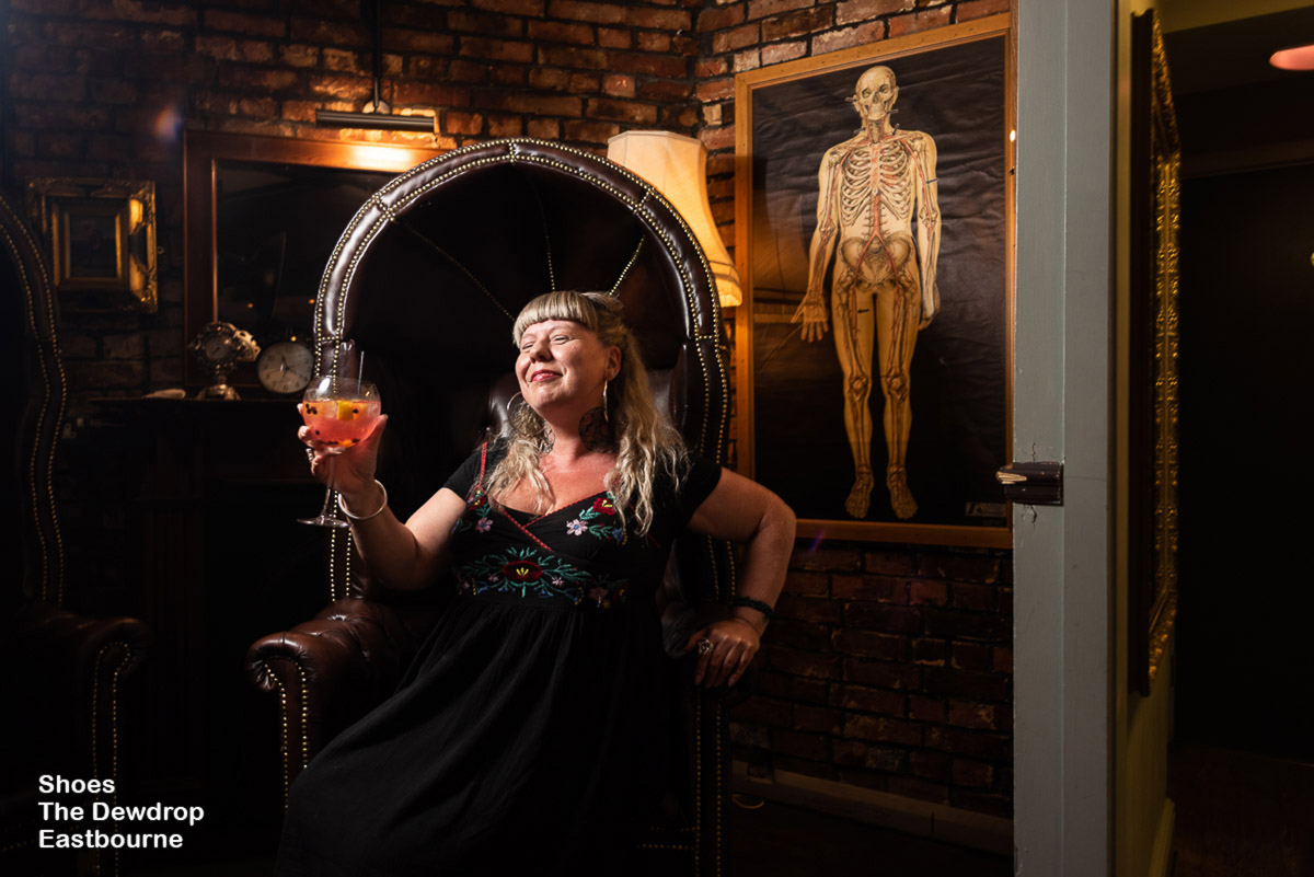 Lady in alternative clothing holds up a gin and tonic in high back chair in great pub