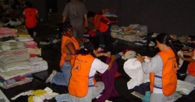 grupo de pessoas dobrando roupas doadas