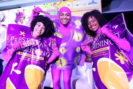 três jovens vestidos com fantasias de camisinha