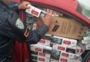 Policial vistoriando carro lotado de cigarros