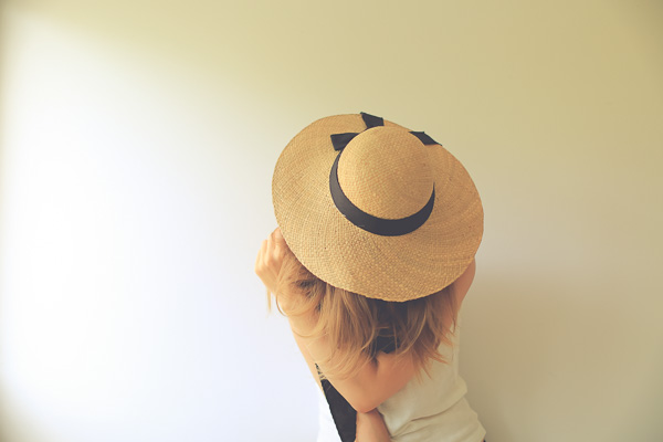 unrecognizable sandy blond woman with a straw hat covering her face