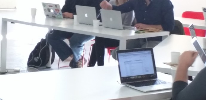 A line of MacBooks on a table