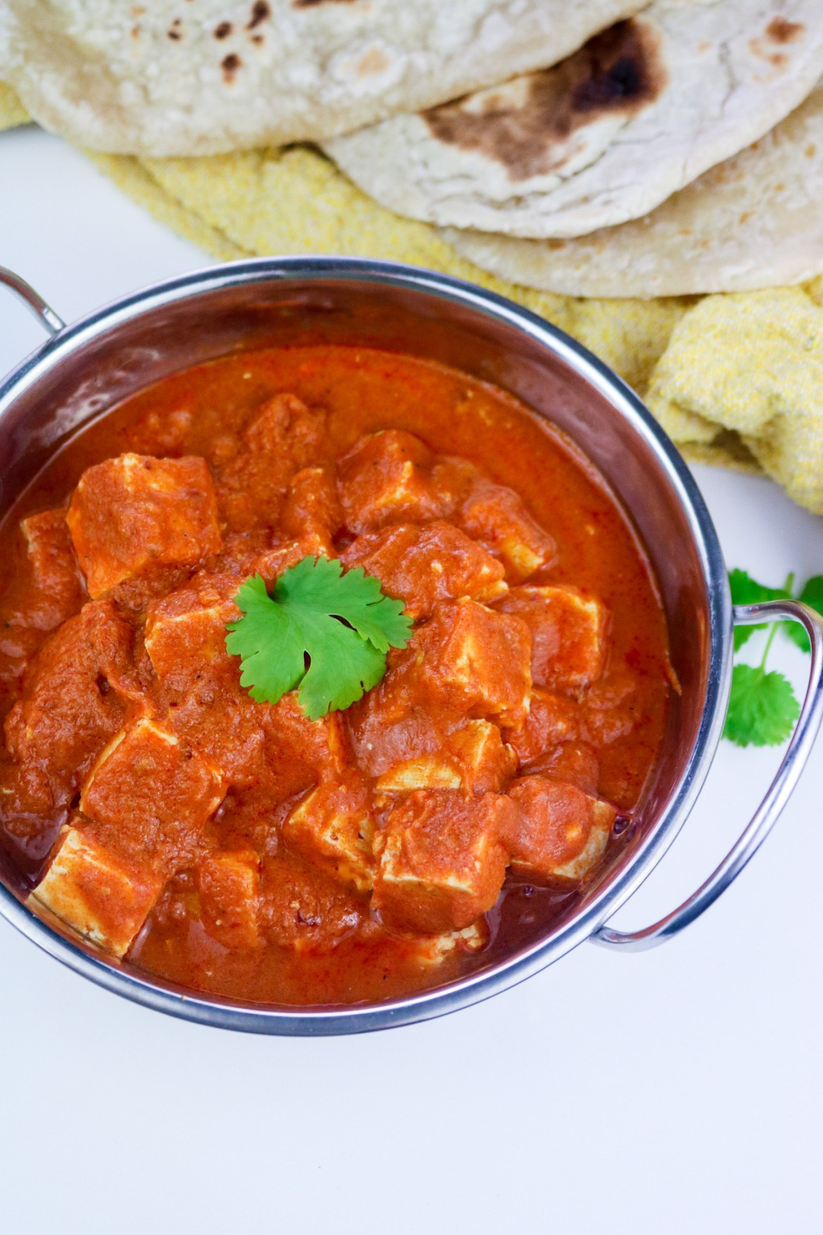 tofu cubes in makhani sauce served into an Indian-style dish decorated fresh coriander leaves and naan bread