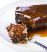 vegan sticky toffee pudding slice on a white plate with fork and oozing toffee sauce