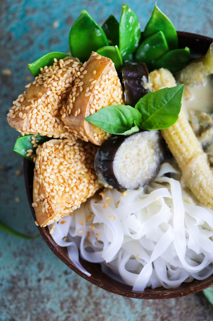 colourful close up on crispy sesame tofu in a bowl with vegan Thai Green Curry and rice noodles