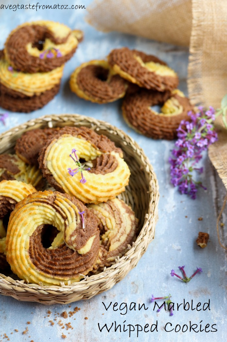 Vegan Whipped Cookies rings with cocoa powder nicely arranged on a wicker plate decorated with puple flowers for Pinterest