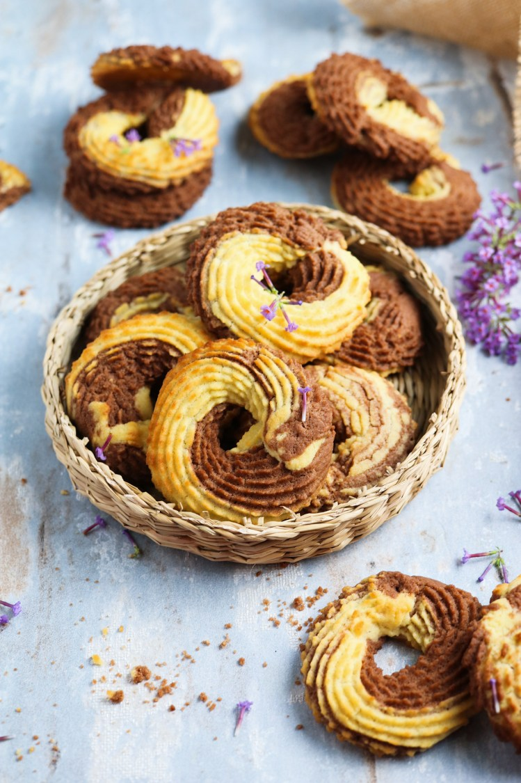 Vegan Whipped Cookies rings with cocoa powder nicely arranged on a wicker plate decorated with puple flowers and crumbles