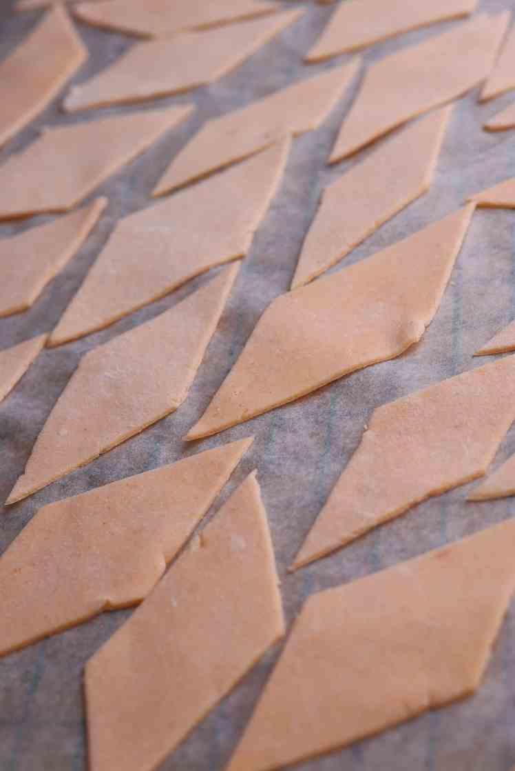 maltagliati di lenticchie rosse allineati su carta da forno