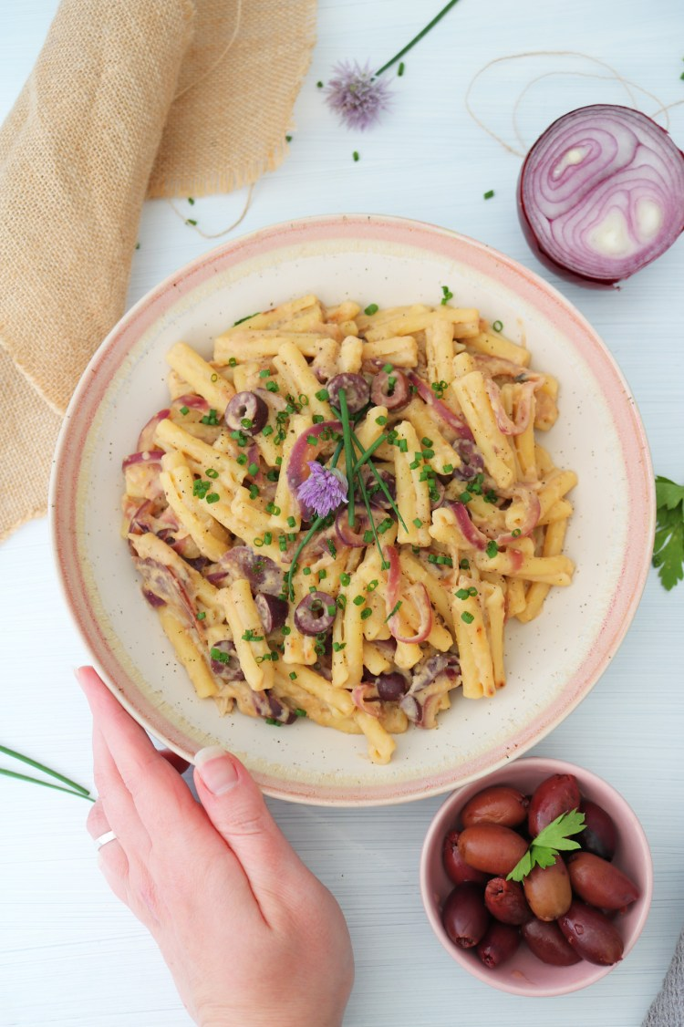 Hummus Pasta Olive and Caramelized Onion hand holding plate