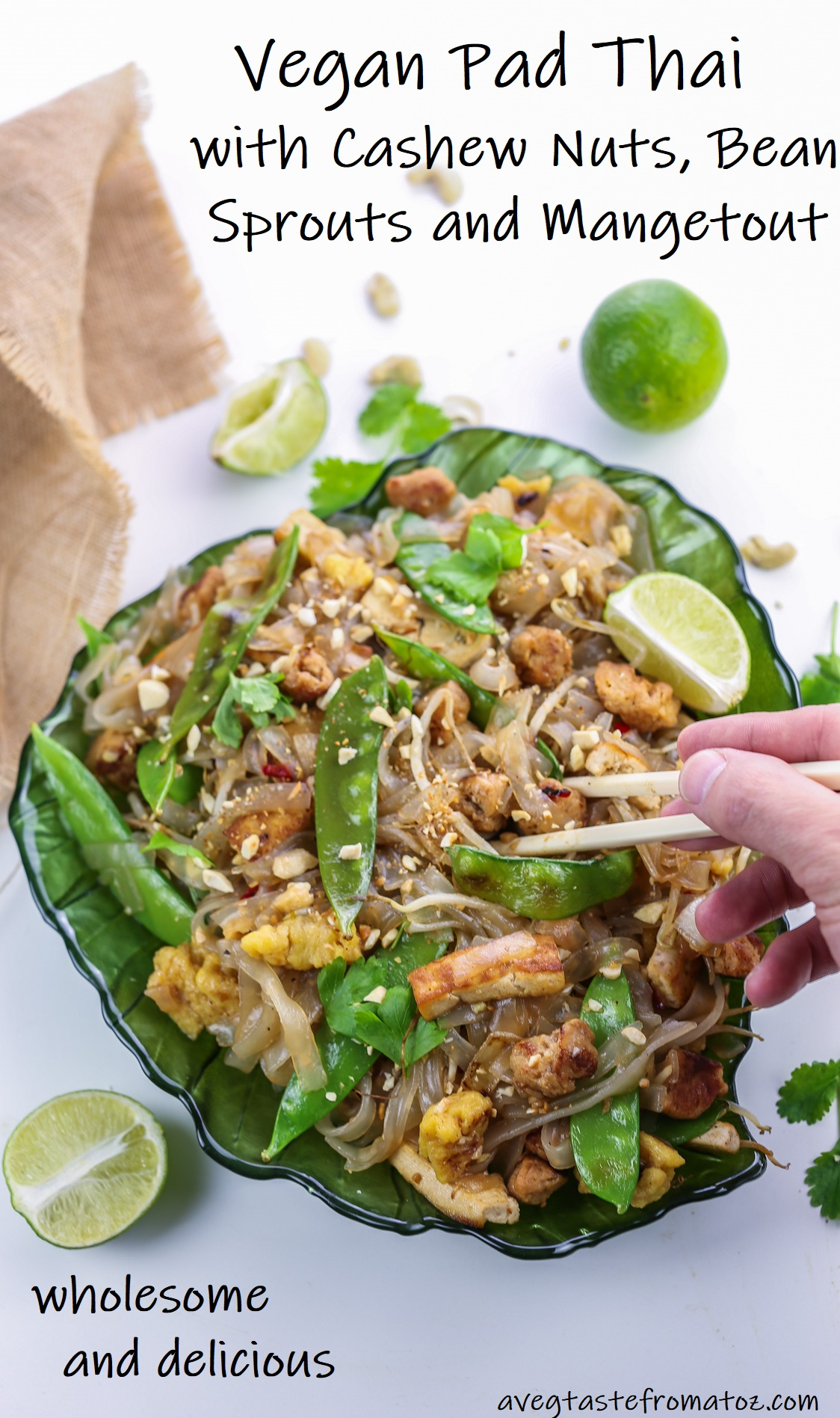 noodles and vegetables pad thai style served on a leaf shaped green plate, topped with cashews, lime wedges and cilantro leaves plate with hand holding chopsticks and black text over picture to be shared on social medias