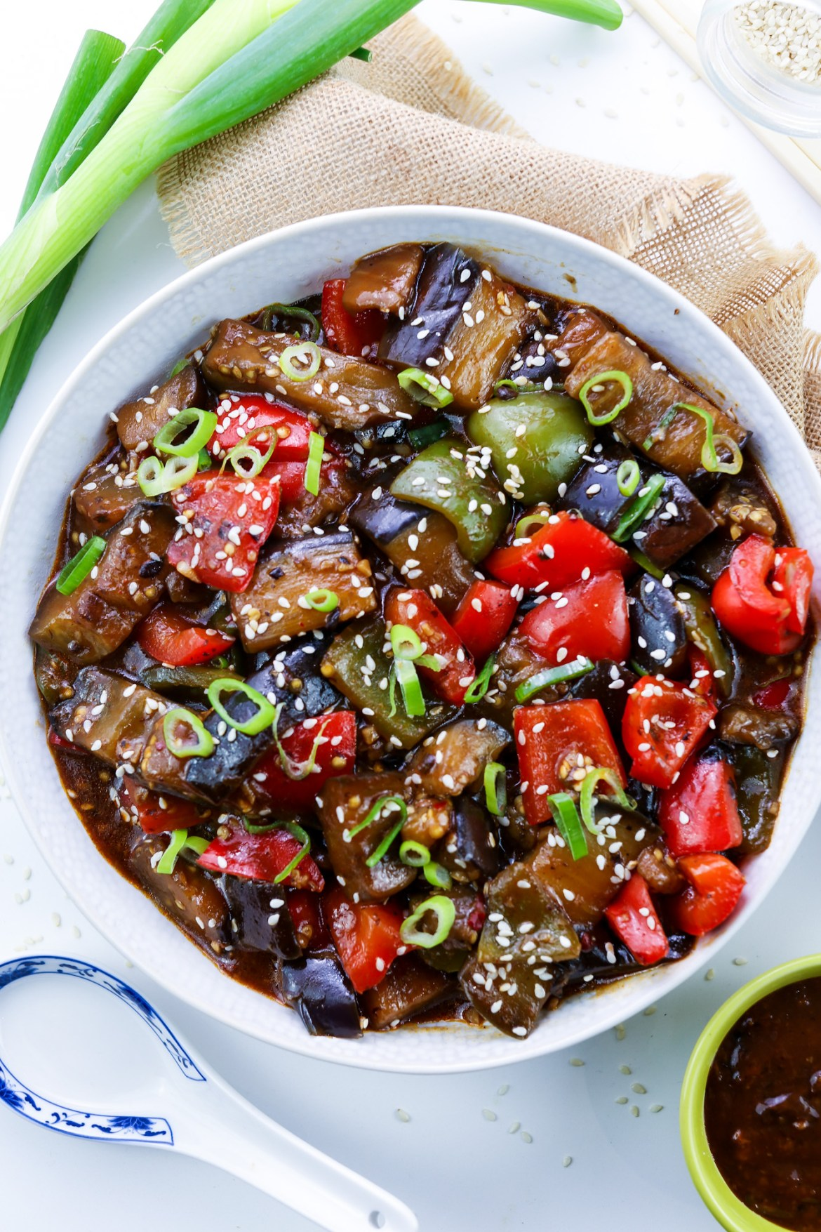 Vegan Aubergine & Peppers in Black Bean Sauce in a white bowl topped with green onions and sesame seeds