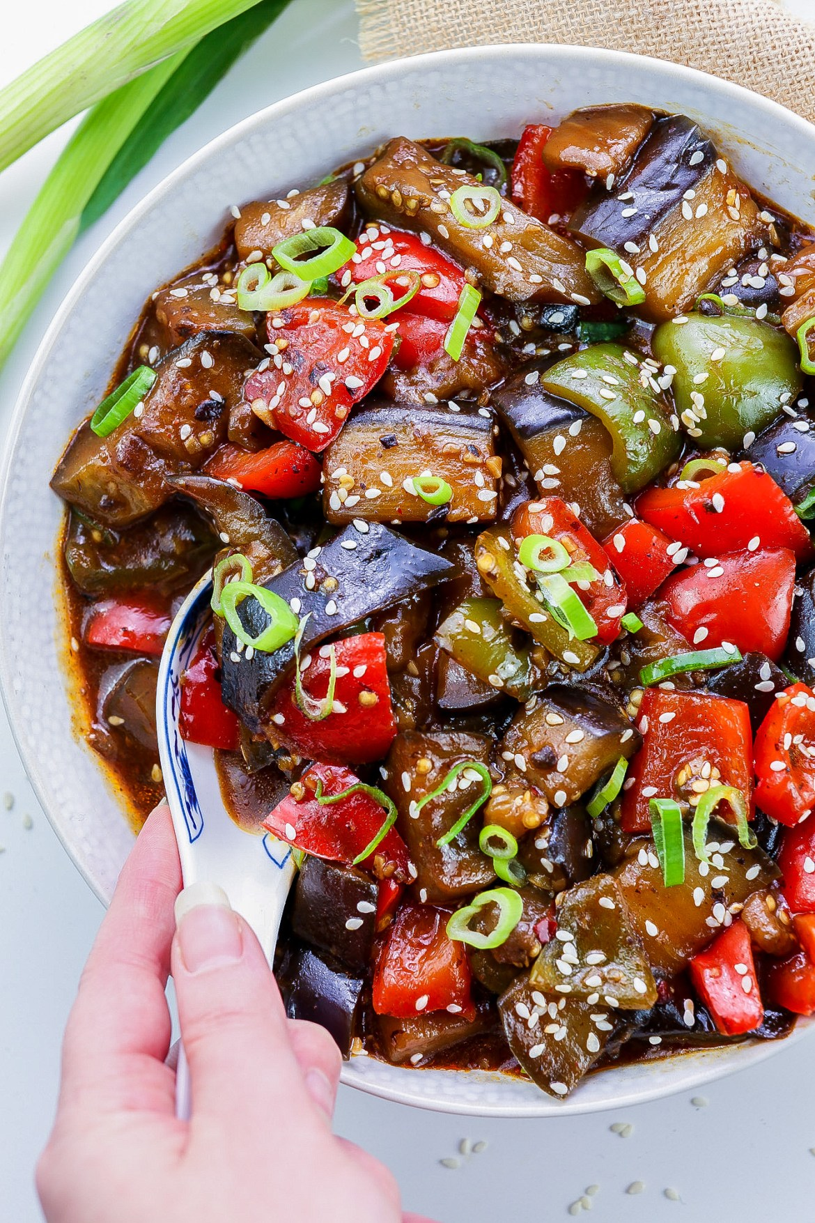 Vegan Aubergine & Peppers in Black Bean Sauce in a white bowl topped with green onions and sesame seeds, and left hand holding a spoonful of the dish