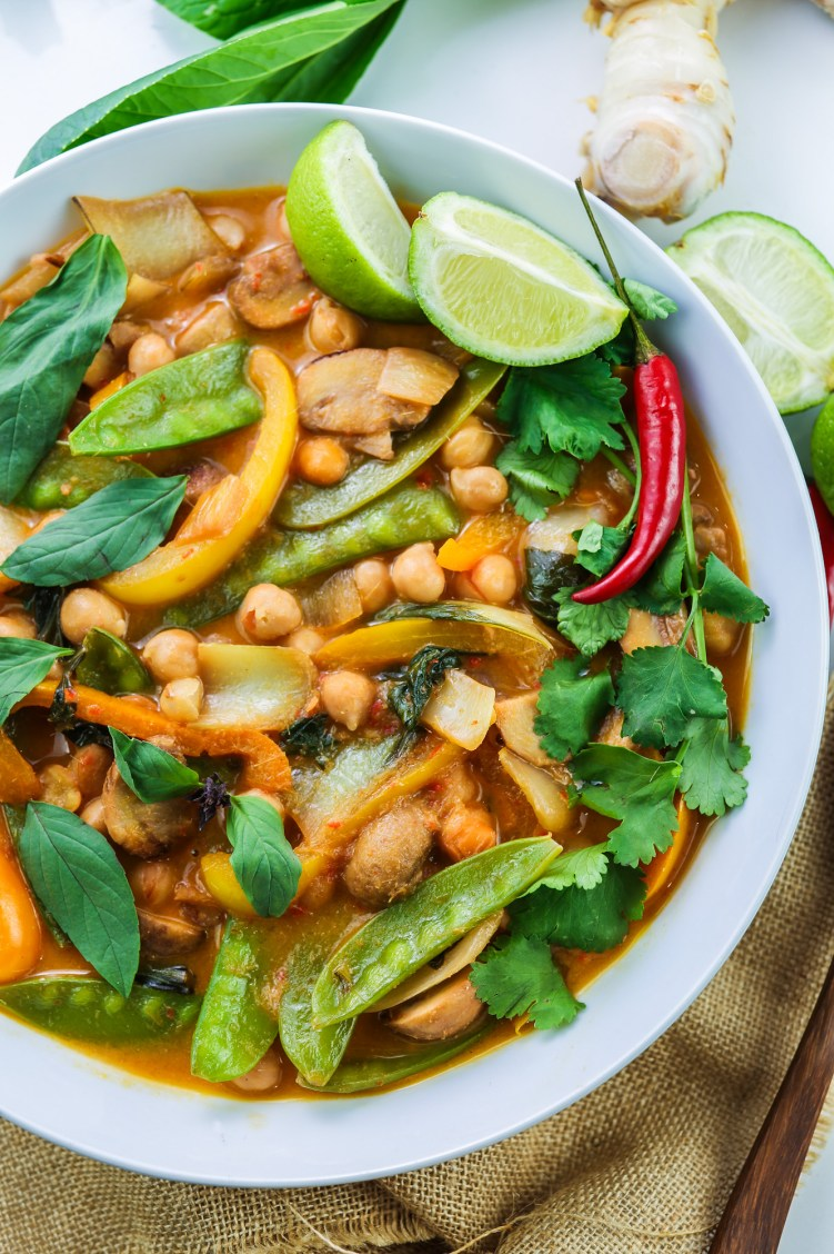 Half White ceramic bowl filled with rich vegan thai red curry with chickpeas, peppers, mangetout, thai basil, coriander leaves and lime wedges