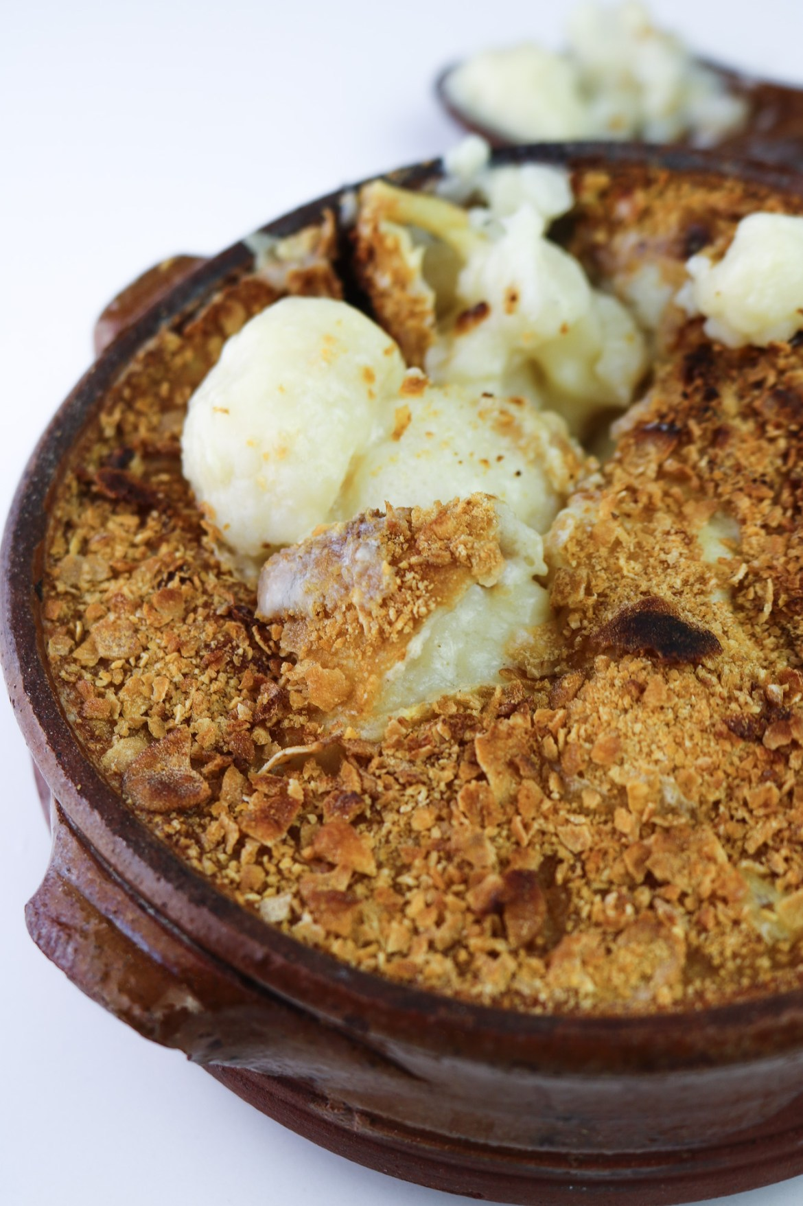 vegan cauliflower cheese close up on baked terracotta pot
