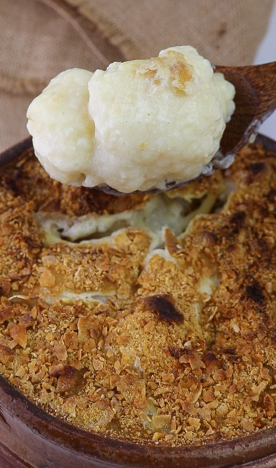 vegan cauliflower cheese close up on wooden spoon