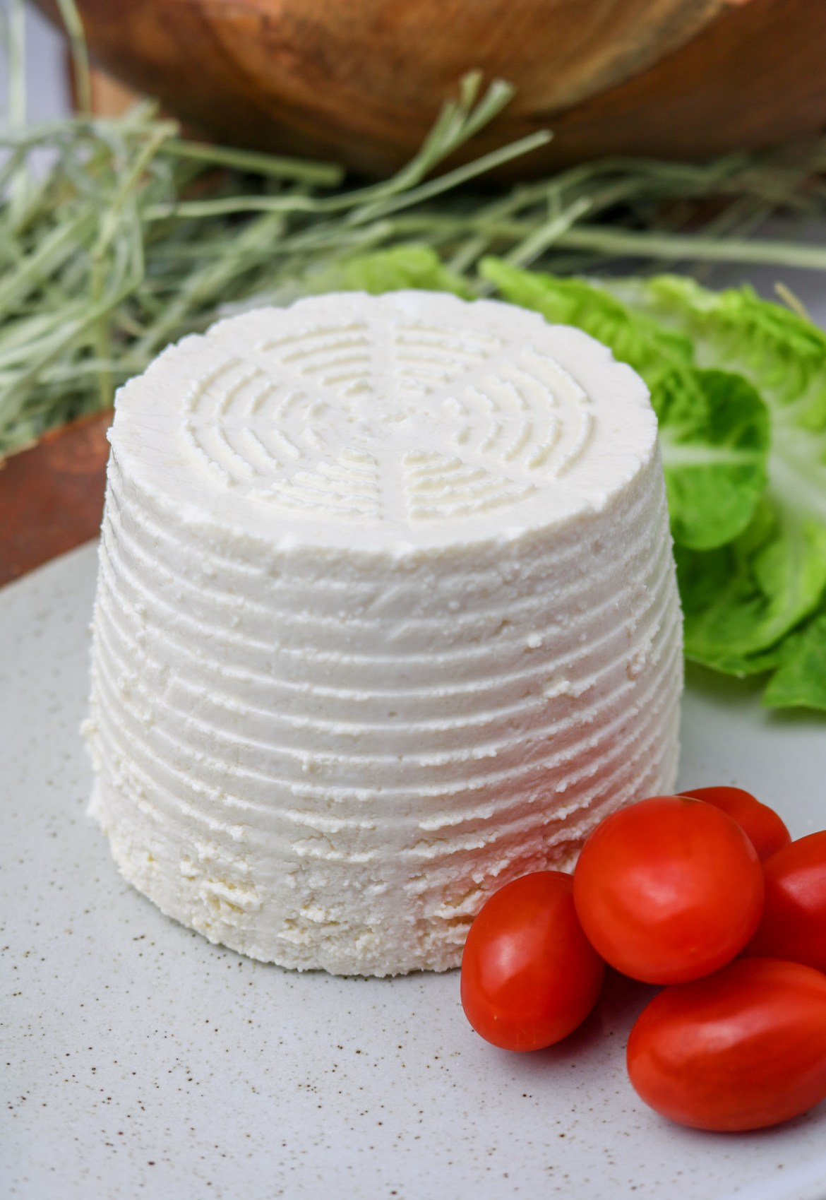 ricotta served on a plate whole with tomatoes and lettuce leaves