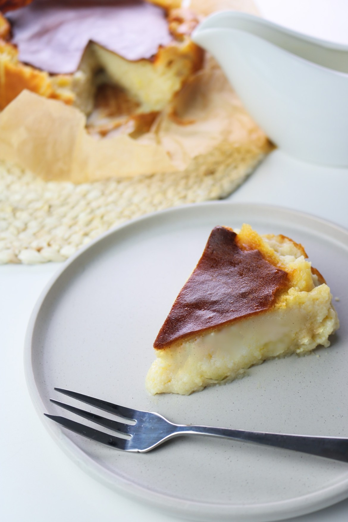 whole vegan burnt basque cheesecake on the background and slice served on a plate with a dessert fork