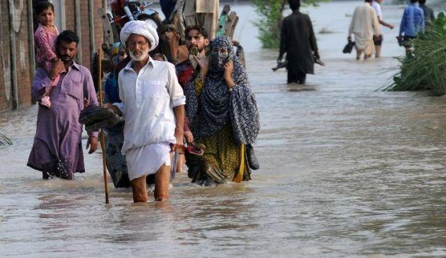 543967-des-pakistanais-marchent-sur-une-route-inondee-le-19-aout-2013-pres-de-lahore