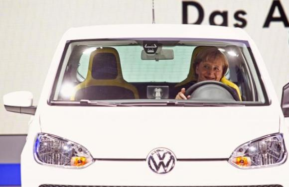 German Chancellor Angela Merkel sits in a Volkswagen eco-up! auto during a visit to the Volkswagen exhibition at the International Motor Show (IAA) in Frankfurt September 15, 2011. REUTERS/Alex Domanski