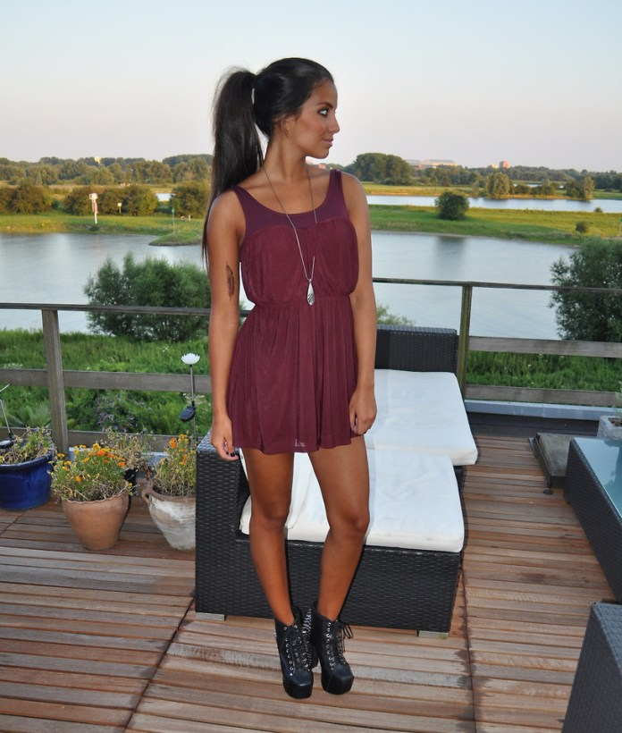 Blogger Stephanie Abu-Sbeih from The Netherlands wears black ankle boots with a burgundy dress