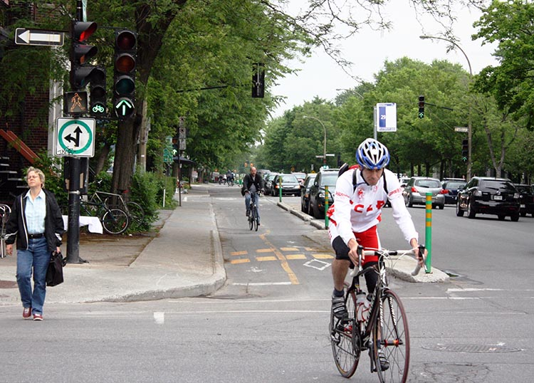 Montreal cycling is safer because the traffic lights are set up to cater to motorists, cyclists, and pedestrians. Montreal Cycling - Separated Bike Lanes