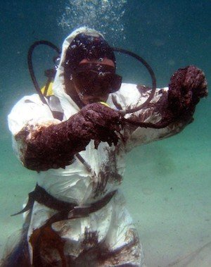 Diver grapples with muck during the BP oil spill