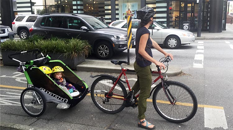 The Amazing Evolution of Vancouver Cycling Infrastructure. Mom and two kids cycle in relative safety on the Dunsmuir Street separated bike lane in downtown Vancouver. The amazing evolution of Vancouver cycling infrastructure