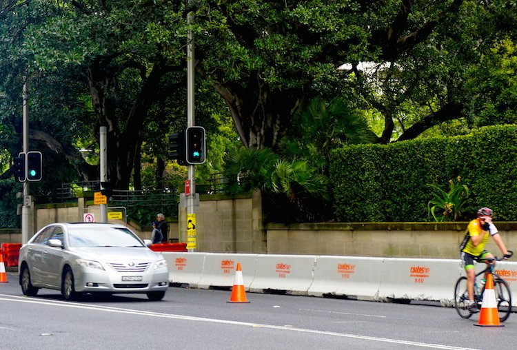 Sydney cycling - A cyclist on College Street. He should be on the OTHER SIDE of the concrete barrier, protected from cars. But he cannot be there, because it is being demolished