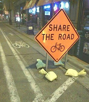 Useful sign - but why block the entire cycle routes with a sign, forcing cyclists out into the car space?